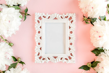 Carved, white frame decorated of white peony flowers on pink background. Peony texture. Flat lay, top view.