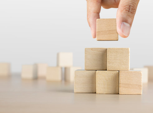 Hand arranging wooden blocks stacking as a pyramid staircase on white background. Success, growth, win, victory, development or top ranking concept.