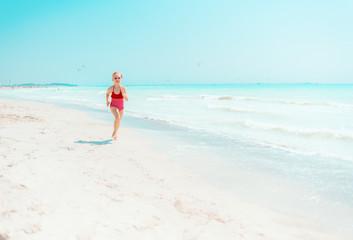 modern girl in red swimwear on seashore jogging