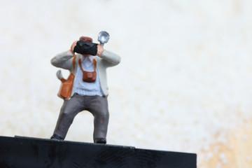 Miniature people take a photo