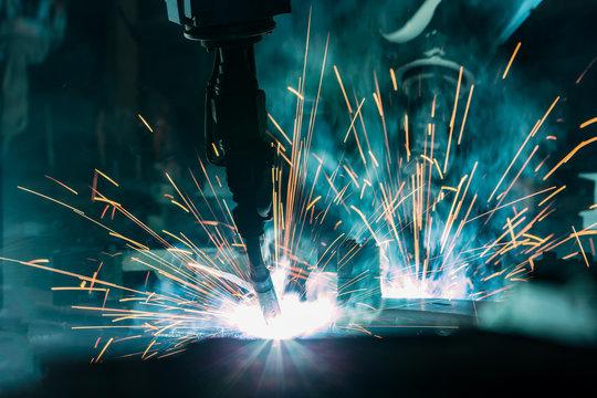 Team industrial robot are welding in factory