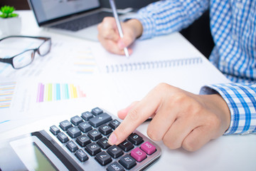 Asian businessmen using a calculator to graph financial charts on the white desk.