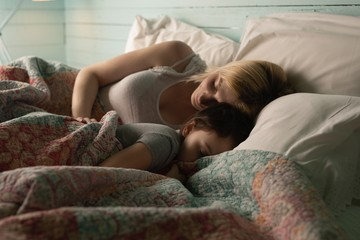 Mother and daughter sleeping in bedroom