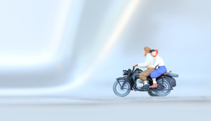 Miniature people bride and groom couple with motorcycle