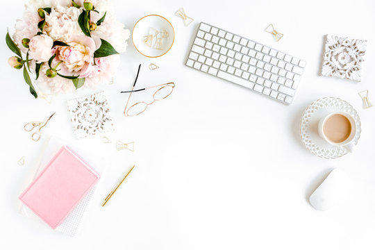 Flat lay women's office desk. Female workspace with computer, pink peonies bouquet, accessories on white background. Top view feminine background.