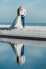 bride and groom on the beach near the fabulous island after the marriage ceremony