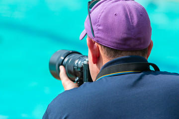 Male photographer taking picture with his camera at a swimming pool
