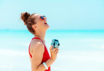 happy modern woman with retro photo camera on seacoast