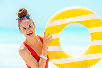 smiling woman on seacoast showing yellow inflatable lifebuoy