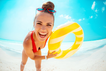 woman with yellow inflatable lifebuoy having fun time on beach