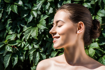 young woman with closed eyes and beautiful smile against green leaves at background