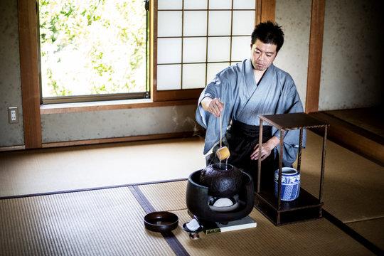 Traditional Japanese Tea Ceremony, man wearing kimono sitting on tatami mat using a Hishaku, a bamboo ladle, to pour hot water.