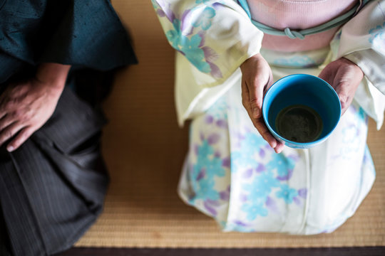 High angle close up of Japanese man and woman wearing traditional white kimono with blue floral pattern kneeling on floor during tea ceremony, holding blue tea bowl.