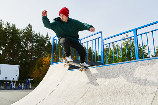 Full length portrait of contemporary young man doing skateboard stunts on ramp in extreme sports park, copy space