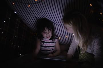 Mother and daughter using digital tablet under blanket