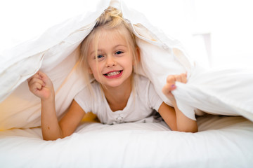 A Cheerful little girl in bed having fun