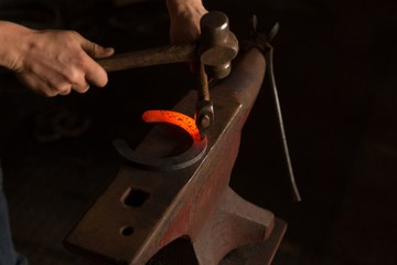 Female metalsmith molding horseshoe in factory
