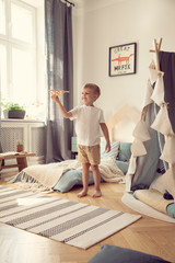 Boy playing with wooden aeroplane in scandinavian bedroom interior with tent and poster. Real photo