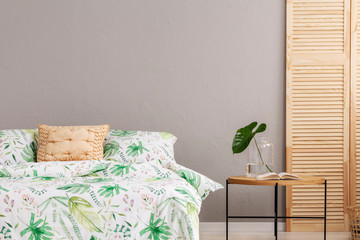 Leaf pattern on duvet in stylish bedroom interior with wooden screen and coffee table with glass vase with monster leaf, real photo with copy space on grey empty wall