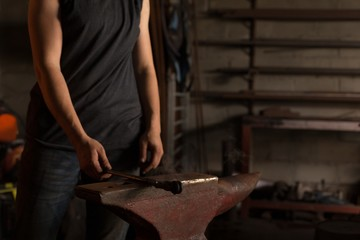 Female metalsmith holding tool in factory