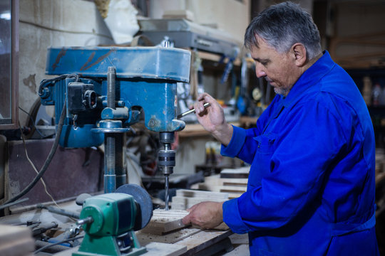 employee drills the item in the workshop with the help of a drilling press