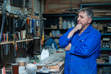 Mature man carpenter in overalls chooses tools in the workshop