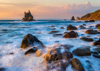 beautiful Benijo beach in Tenerife, waves crashing against boulders during sunset