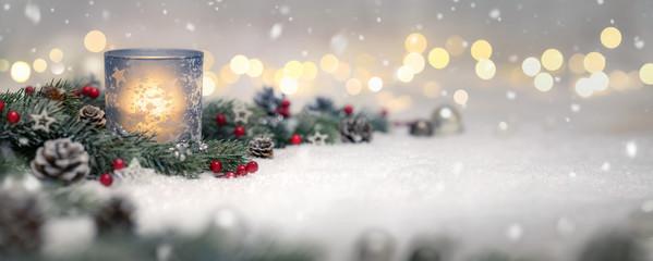 Dekoration für Weihnachten mit Kerze, Lichtern und Tannenzweigen auf Schnee