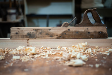 Plane on the carpenter's table in the workshop with sawdust