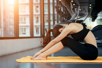 Asian woman exercising in the gym, Young woman workout in fitness for her healthy and office girl lifestyle. She is sitting and playing yoga.