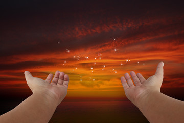 Human hands pray with sunset background.