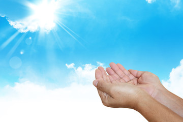 Human hands pray with blue sky