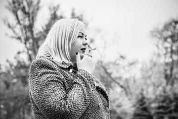 A pretty big European girl with overweight smokes in an outdoor . Problems of smoking among women. The effect of smoking on weight and shape