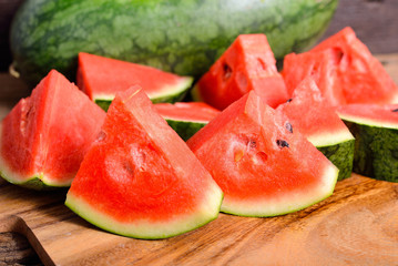 whole and portion cut watermelon on wooden cutting board