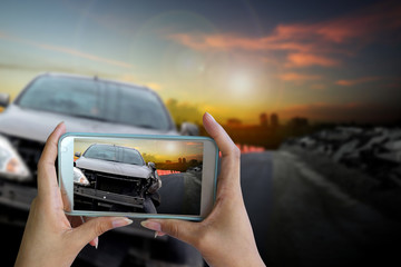 Hand of woman holding smartphone and take photo of car accident.