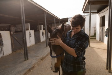 Woman stroking horse at stable