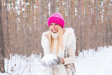 Winter, beauty and fun concept - young blond woman walking in the winter forest and throwing snow up