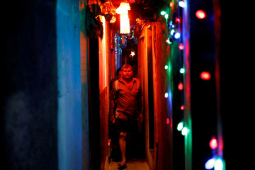 Residents walk in a slum's alley illuminated by colorful lights on the eve of the Hindu festival of Diwali in Mumbai