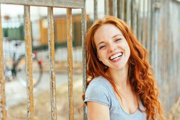 Pretty vivacious young woman grinning at camera