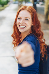 attractive redhead woman pointing at the camera