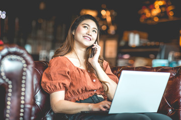 Beautiful Attractive Asian woman working with laptop smile and talking with customer in smartphone to get idea and requirement for success job outside office in coffee shop,Business Concept,Warm Tone
