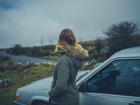 Woman standing by her car on the moor