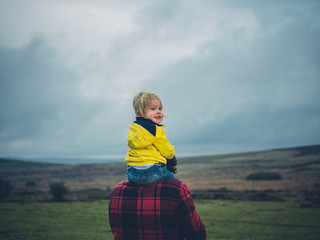 Toddler riding on father's shoulders on the moor