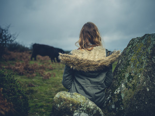 Woman on the moor looking at cow