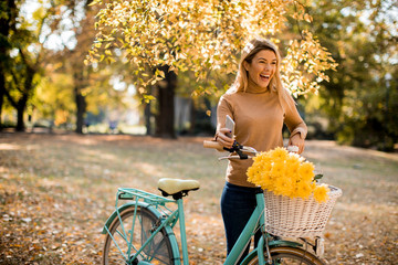 Happy active woman riding bicycle in autumn park Wall mural