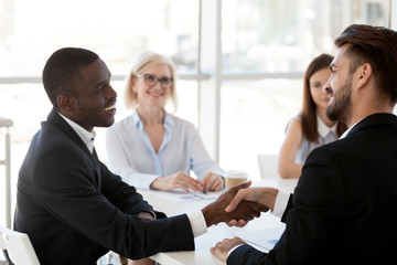 Caucasian businessman shake hand of black colleague greeting at briefing in office, diverse employees handshake introducing or getting acquainted at meeting, boss congratulate coworker with success