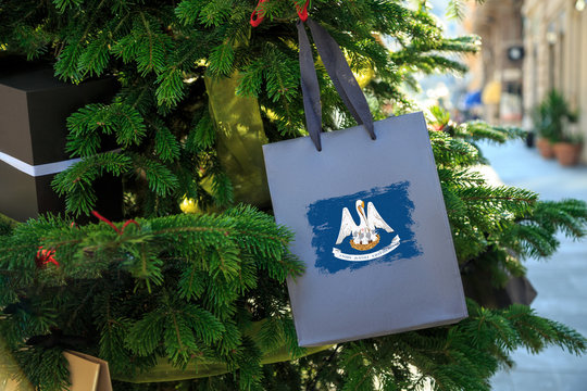 Louisiana state flag printed on a Christmas shopping bag. Close up of a shopping bag as a decoration on a Xmas tree on a street. New Year or Christmas shopping, local market sale and deals concept.