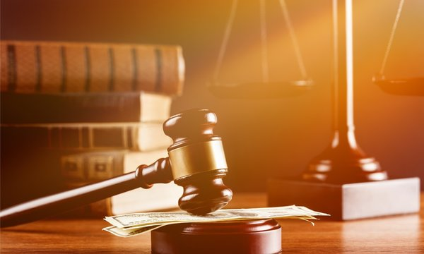 Justice Scales and books and wooden gavel with money on table