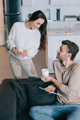 smiling young couple with cups of cocoa and tablet relaxing together at home