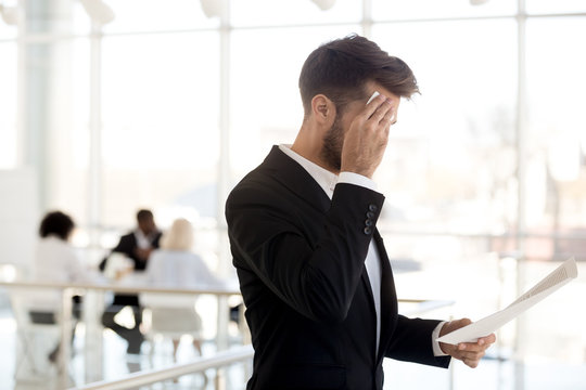 Stressed man sweat using wipe worry about business interview, frustrated male employee reading papers prepare for hiring at corporation, nervous worker review cv before talk with recruiters in office